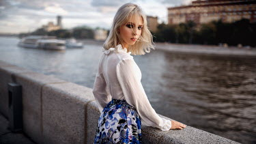 Georgy Chernyadyev SERIOUS BLONDE WOMAN STANDING BY URBAN RIVER