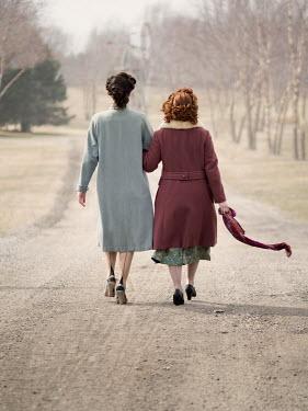 Elisabeth Ansley TWO RETRO WOMEN WALKING ARM IN ARM OUTDOORS