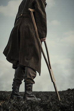Magdalena Russocka close up of wounded wartime soldier with crutches standing in field