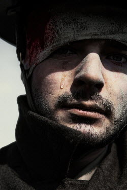 Magdalena Russocka close up of crying wounded wartime soldier covered with mud outside