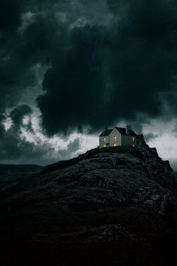 Nic Skerten Cottage on hill under stormy sky