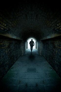Nic Skerten Silhouette of man running in tunnel