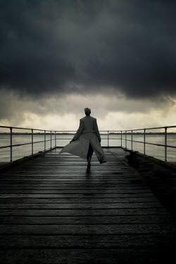 Nic Skerten 1940s woman in vintage coat walking on seaside pier