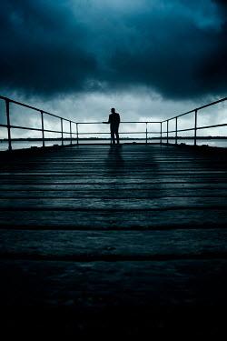 Nic Skerten Silhouette of man standing on pier