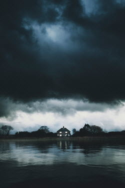 Nic Skerten Cottage by lake under stormy sky
