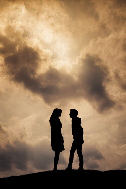Nic Skerten Silhouette of young woman and boy on hill under stormy sky