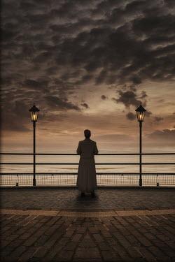 Nic Skerten 1940s woman in coat by pier railings at dusk