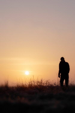 Tim Robinson Silhouette of man walking in field at sunset