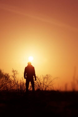 Tim Robinson Silhouette of man standing in field at sunset