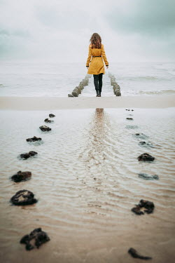 Natasza Fiedotjew woman in yellow coat walking on beach