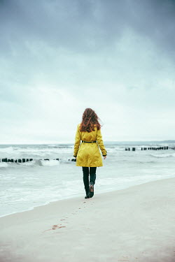 Natasza Fiedotjew woman in yellow coat walking on beach