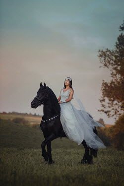 Anna Sychowicz Young woman in white dress on black horse