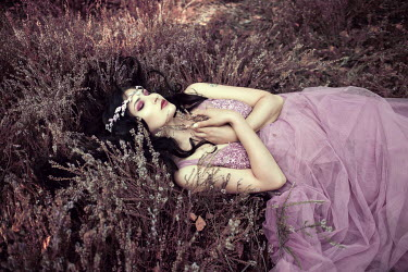 Anna Sychowicz Young woman in purple dress lying in flowers