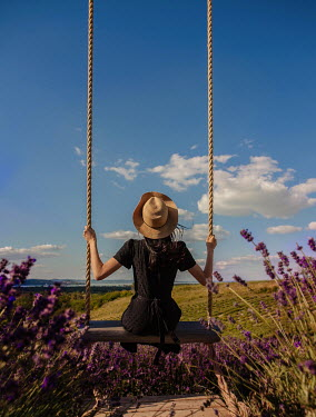 Nikaa Young woman in hat and black dress sitting on swing in lavender field