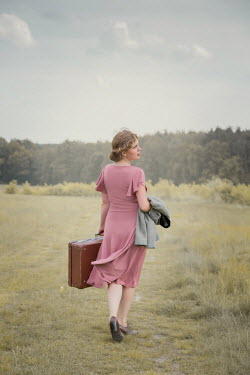 Joanna Czogala Young woman in 1940s pink dress walking in field with suitcase