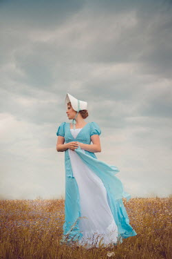 Joanna Czogala Young woman with Victorian blue dress and bonnet in field