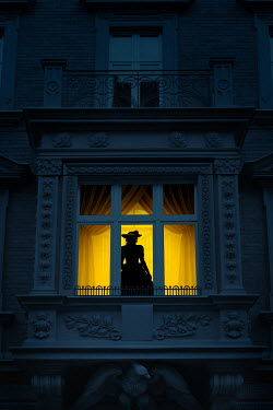Magdalena Russocka silhouette of victorian woman in illuminated window of palace at night