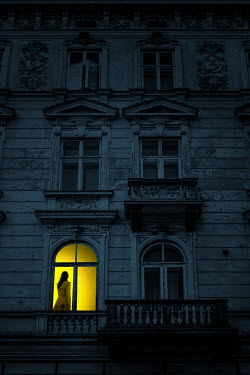Magdalena Russocka modern woman in illuminated window of old townhouse at night