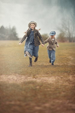 Anna Buczek HAPPY GIRL AND BOY HOLDING HANDS IN COUNTRYSIDE