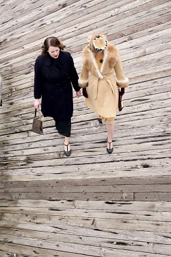 Elisabeth Ansley TWO RETRO WOMEN WALKING ON PIER