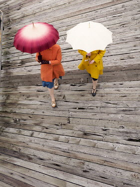 Elisabeth Ansley TWO WOMEN WALKING ON PIER WITH UMBRELLAS
