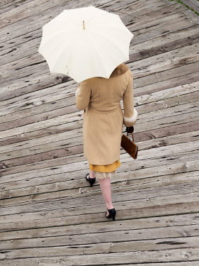 Elisabeth Ansley RETRO WOMAN WITH UMBRELLA WALKING ON PIER