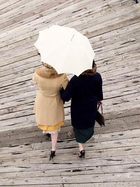 Elisabeth Ansley RETRO WOMEN WALKING ON PIER WITH UMBRELLA