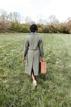 Matilda Delves WOMAN WITH COAT AND SUITCASE WALKING IN FIELD