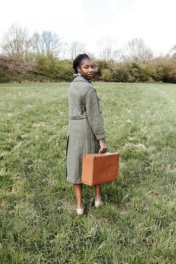 Matilda Delves WOMAN WITH COAT AND SUITCASE IN FIELD