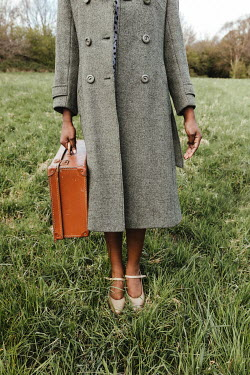 Matilda Delves WOMAN WITH COAT AND SUITCASE STANDING IN FIELD