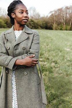 Matilda Delves RETRO WOMAN WITH COAT STANDING IN COUNTRYSIDE