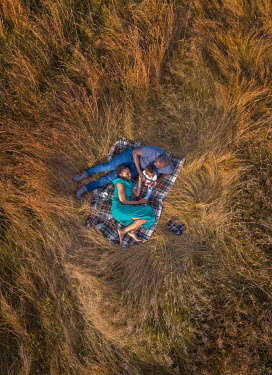 Mary Wethey PARENTS WITH BABY LYING ON RUG IN FIELD