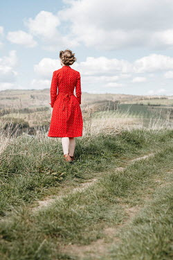 Shelley Richmond WOMAN IN RED DRESS STANDING IN COUNTRYSIDE