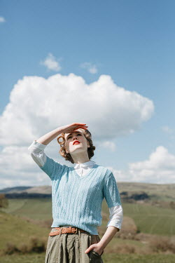 Shelley Richmond RETRO WOMAN IN COUNTRYSIDE WATCHING SKY
