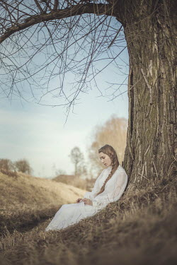 Anna Sychowicz DAYDREAMING GIRL SITTING BY TREE IN COUNTRYSIDE