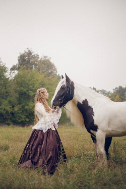 Anna Sychowicz HISTORICAL WOMAN STANDING WITH HORSE IN FIELD