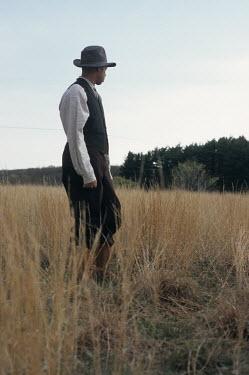 Debra Lill HISTORICAL MAN IN HAT STANDING IN FIELD