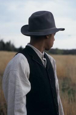 Debra Lill HISTORICAL MAN IN HAT AND WAISTCOAT IN FIELD