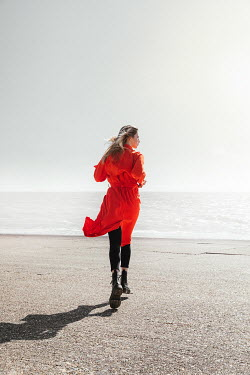 Matilda Delves WOMAN IN RED COAT RUNNING BY SUNLIT SEA