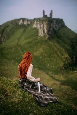 Rebecca Stice WOMAN WITH RED HAIR AND DAGGER SITTING ON HILL