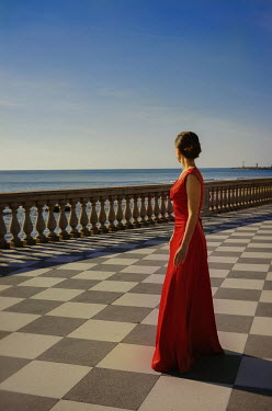 Nikaa WOMAN IN RED DRESS ON TERRACE BY SEA