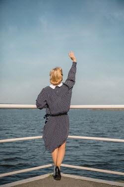 Joanna Czogala BLONDE WOMAN WAVING AT SEA BY RAILINGS