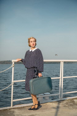 Joanna Czogala BLONDE WOMAN WITH SUITCASE BY SEA RAILINGS