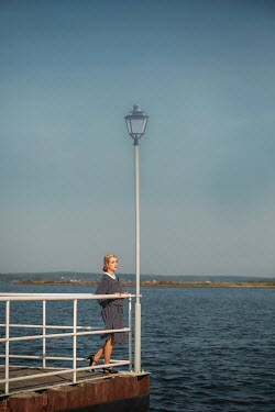 Joanna Czogala BLONDE RETRO WOMAN BY RAILINGS AND SEA