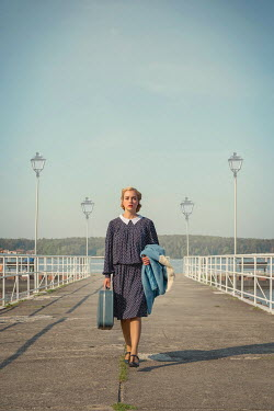 Joanna Czogala BLONDE WOMAN WITH SUITCASE WALKING ON JETTY