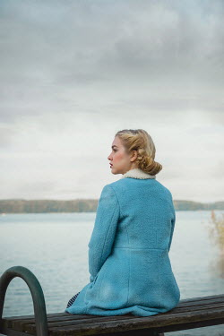 Joanna Czogala BLONDE WOMAN IN BLUE COAT SITTING BY RIVER
