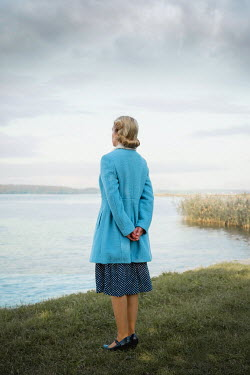 Joanna Czogala BLONDE WOMAN IN BLUE COAT STANDING BY RIVER