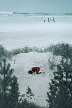 Natasza Fiedotjew young woman in red dress lying on sand dune passed by group of people