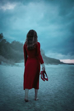 Natasza Fiedotjew woman in red dress holding high heels walking on beach at sunset