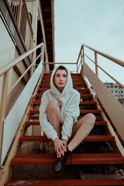 Greta Larosa GIRL IN HOODED JACKET SITTING ON STEPS OUTDOORS